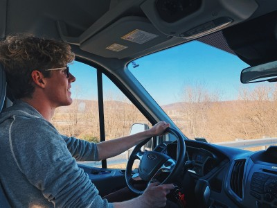 A young man driving a van on a highway, photographed from the passenger's seat.