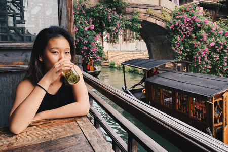 Jodi Ann Wang drinks a glass of tea at a table while outside a boat passes on a canal, underneath a footbridge covered in pink flowers.