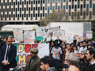 A large group of protestors holding signs gather in a plaza in front of a large building.