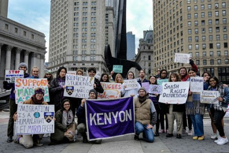 """A group of protestors pose with a large purple """"Kenyon"""" banner."""